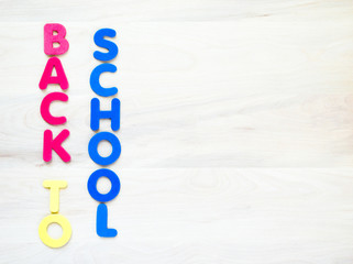 colorful foam letters spelling the words Back to School in vertical rows on a wooden desk with copy space