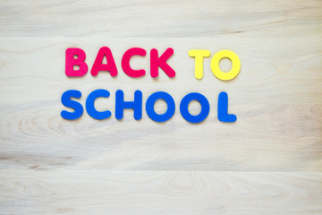 colorful foam letters spelling the words Back to School on a wooden desk with copy space