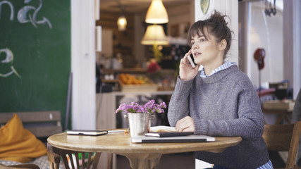 A young surprised cute happy brunette girl dressed in a grey pullover is having a call in a cafe