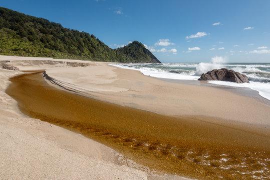 Tannin coloured stream flowing over sandy Scotts Beach, Karamea, New Zealand.