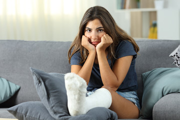 Frustrated disabled woman with plaster foot looking at you