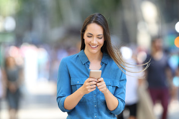 Happy woman writing message in a smart phone on the street