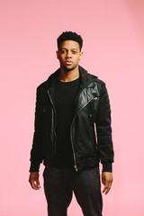 Vertical portrait of a young, cool man in black, standing, isolated on pink background