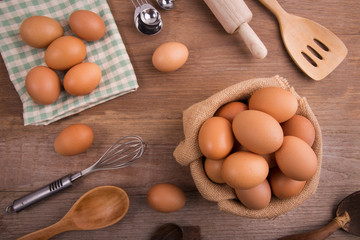 Fresh farm eggs on a wooden rustic background, Whipping eggs and whisk,top view with copy space