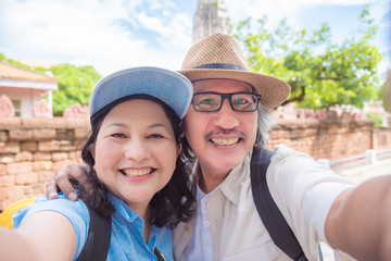 Happy asian retired couple taking their photo by smart phone at a temple in Thailand.