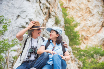 Retired asian couple sitting on the hill and smile together