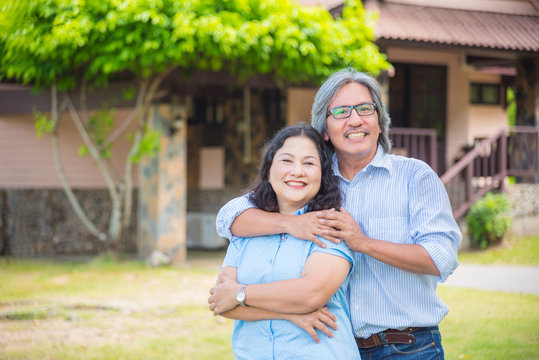Retired couple standing in front of their house and smile happily