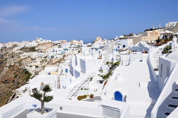 Famous stunning view of white architectures and colorful houses above the volcanic caldera in the village of Oia in Santorini island, Greece