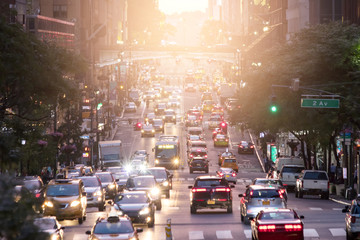 Fotomurales - Crosstown traffic on 42nd Street in Midtown Manhattan New York City with sunlight in background