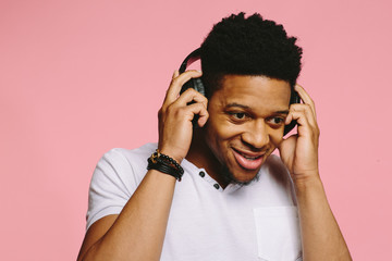 Portrait of a smiling guy in white shirt listening to music on pink background