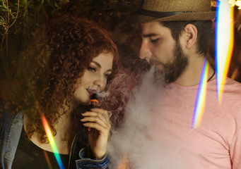 Loving couple on date. Guy and girlfriend smoke electronic cigarettes. He blows clouds of smoke. Red-haired girl. Man in hat and t-shirt. Lights of night city shine.