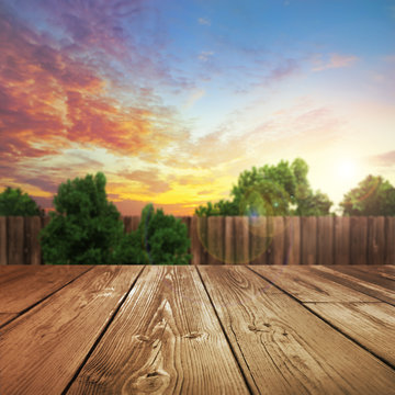 wooden table top with blurred outdoor backyard background