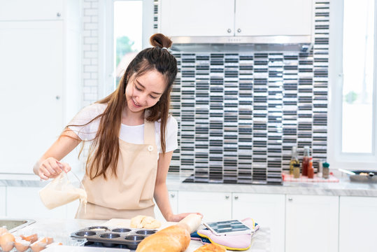 Asian woman cooking and baking cake in kitchen alone happily. People and lifestyles concept. Food and drink theme. Interior decoration theme.