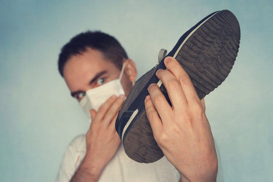Man with mask is holding dirty stinky shoe - unpleasant smell concept. Dirty smelly sneakers.