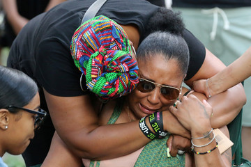Mother of rapper Smoke Dawg is consoled during a vigil in Toronto