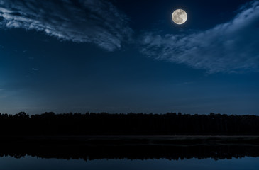 Blue sky and full moon at seaboard. Serenity nature background.