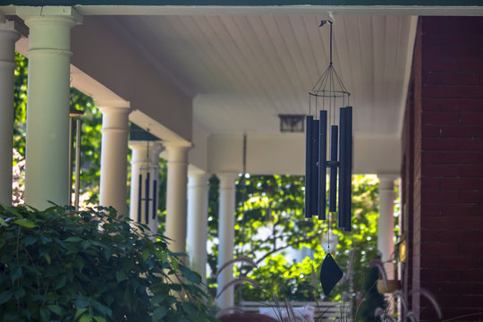 Wind chimes on a house with white pillars