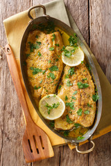 Delicious fish: baked trout fillets with garlic buttery herb sauce, lemon and parsley close-up in a copper pan. Vertical top view