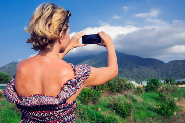 Woman using smart phone take a photo mountain view