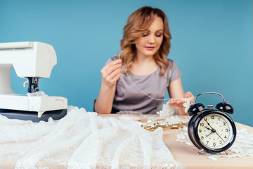 attractive blonde hairstyle woman seamstress tailor ( dressmaker) designer wedding dress sews beads to lace behind the table with sewing machine on a blue background in the studio