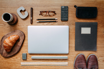 Stylish and modern composition of wooden desk with laptop, phone, shoes notebook, glasses and office accessories. Creative desk of traveler.