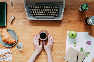 Stylish and modern wooden desk with typewriter, croissant,woman hands on cup of coffee notebooks, succulents and office accessories. Home office of romantic writer or poet. Flat lay concept.