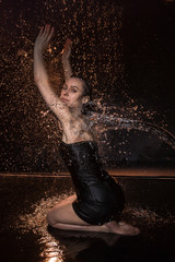 Girl in black dress in water in a small pool, stream of water flying to her and black background