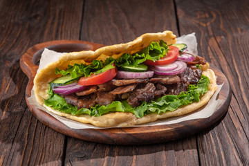 Delicious fresh homemade sandwich with chicken burspit roasted meat, tomato, onions and lettuce on wooden board on dark wooden table. Doner kebab. Healthy food concept.