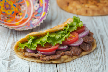 Delicious fresh homemade sandwich with chicken burspit roasted meat, tomato, onions and lettuce on wooden board on white wooden table. Doner kebab. Healthy food concept.