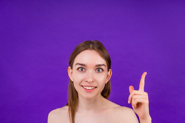 portrait of a beautiful clean woman skin smiling with a toothy smile finger pointing up on a violet background in the studio copyspace