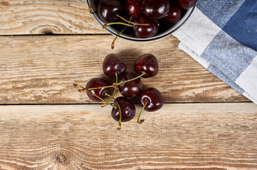 Cherries in a white bowl next to a doily and a few cherries in front, on a wooden background, flat lay