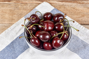 Cherries in a white bowl next to doily, on wooden background