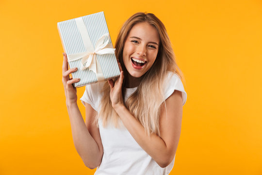 Portrait of an excited blonde young woman holding present