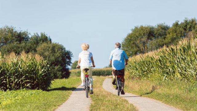 Full length of a senior active couple smiling and looking forward with confidence and serenity while riding bicycles in the countryside in summer