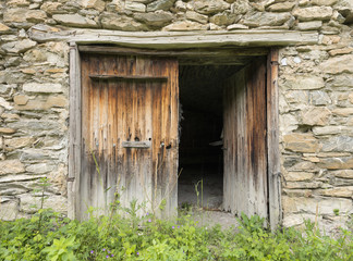 old wooden brown doors of stone barn in french haute provence