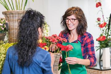 Floristin bedient freundlich lächelnd eine Kundin im Blumenladen