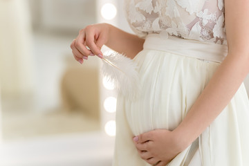 Belly of a pregnant woman holding a white feather