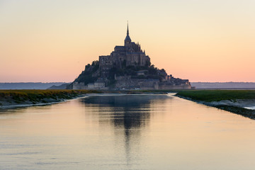 The silhouette of the famous Mont Saint-Michel tidal island in Normandy, France, at sunrise and high tide, reflecting in the still waters of the Couesnon river with the warm colors of the sky.
