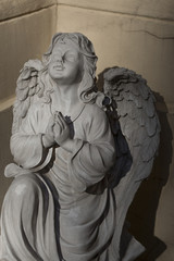 Statue of a white stone praying angel