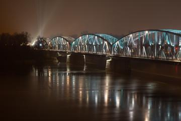 Jozef Pilsudski road bridge at night reflected in Vistula river. Torun, Poland. Europe.