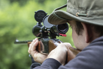 A Man Looking through a scope on a hunting rifle close up