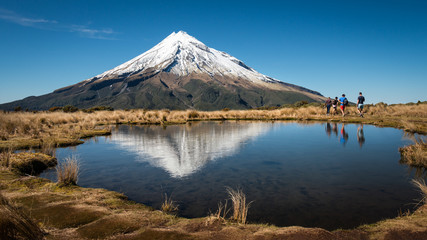 Hiking Pouakai Track with Mount Taranaki reflected in the water, Egmont National Park