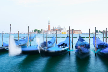 Colorful landscape with clear sky on piazza San Marco in Venice. Row of gondolas parked on city pier. Church of San Giorgio Maggiore on background, Italy, Europe