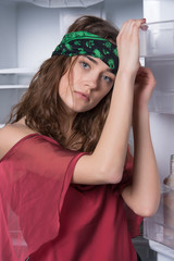Girl leaning on open fridge door. Skinny model in kitchen, diet concept. Woman with beautiful green eyes and long curly hair. Female hipster wearing head band. Lady in boho style blouse