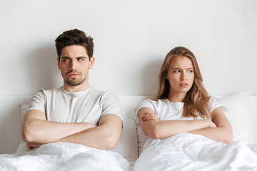Negative offended loving couple lies in bed quarrel.