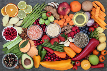 Health food selection with fresh vegetables, fruit, herbs, spices, grains, seeds, himalayan salt and olive oil. Super foods very high in antioxidants and vitamins.