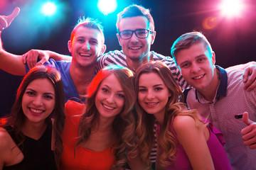 Happy guys and girls are having fun in a nightclub