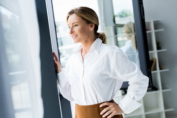 attractive businesswoman looking at window in office