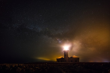 Lighthouse shining in the night of stars.