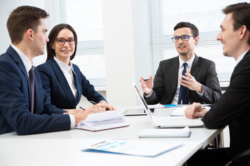 Business people are sitting around the table at a meeting in the office
